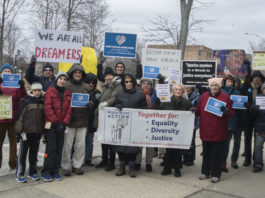 """Residents briefly held up signs protesting Trump administration policies on Martin Luther King's birthday, saying things like """"We are all immigrants"""" and """"The opposite of love is not hate... It's indifference."""" (Photo by Janelle Clausen)"""