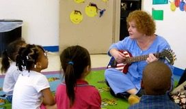 Marilyn Hoffman, well known for her songs and guitar, teaches a group of young students through song. (Photo courtesy of Barbara Masry)