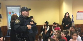 Silverstein Hebrew Academy students listen as police officers from the Great Neck Estates Police Department explain the lifesaving nature of Kevlar vests, and some of the dangers police officers face on a daily basis. (Photo courtesy of Zimmerman/Edelson)