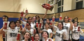 Members of Silverstein Hebrew Academy's Girls Basketball Lady Sharks team hold their championship trophies on the court, celebrating an undefeated season and championship victory. (Photo courtesy of Silverstein Hebrew Academy)
