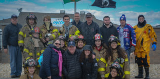 """Erin Lipinsky, flanked by supporters and members of the Alert Fire Company, came down to Tobay Beach to be """"freezin' for a reason."""" (Photo by Janelle Clausen)"""