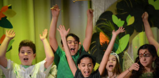Peter Pan, portrayed by Rafaella Sarraf, leads the Lost Boys and others in cheers. (Photo by Janelle Clausen)