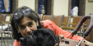 Local artist Suzanne Posner poses with her service dog Brianna in the Great Neck Plaza courtroom, where her work will be on display until the end of May. (Photo by Janelle Clausen)