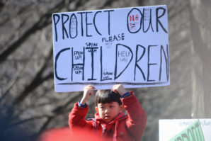 A boy perched atop a parent's set of shoulders holds up a sign calling on legislators to protect the children and speak up against guns. (Photo by Janelle Clausen)