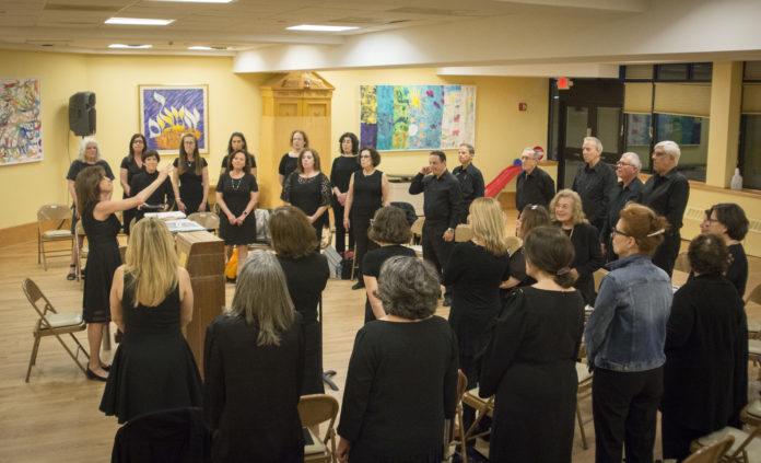 Deborah Tartell, who previously worked as a choral teacher for more than three decades, leads dozens of people through rehearsal. (Photo by Janelle Clausen)