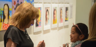 Ellen Schiff, the head of school at the Gold Coast Arts Center, greets one of her students at the opening reception of the Festival of the Arts gallery. (Photo by Janelle Clausen)