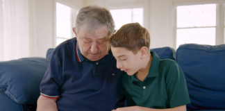 """Elliot and Jack, a Holocaust survivor, sit together on the couch while going through an old photo album in """"The Number on Great-Grandpa's Arm."""" The film will be shown on April 22. (Photo courtesy of HBO documentary films)"""