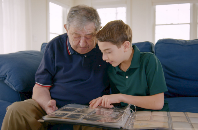 Elliot and Jack, a Holocaust survivor, sit together on the couch while going through an old photo album in