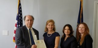 David Aubrey accepts the National Library Workers' Day Nominee Certificate awarded posthumously to his brother, Jon Aubrey, and presented by Senator Elaine Phillips. (Photo courtesy of the Great Neck Library)