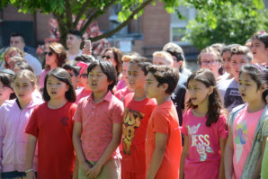 Students garbed in pink, maroon, and red sing as part of a ceremony for Zachary Portnoy's garden. (Photo by Janelle Clausen)