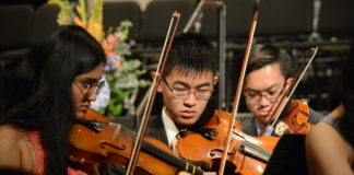 A trio of students in the Great Neck North Symphony Orchestra practice before commencement begins. (Photo by Janelle Clausen)