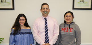 North High Principal Daniel Holtzman congratulates Courtney Hakimian and Megan Xu on being National Merit Scholars. (Photo courtesy of the Great Neck Public Schools)