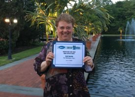 Judy Epstein holds up her award for excellence in humor column writing. (Photo courtesy of Judy Epstein)