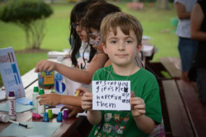 Sam Bernstein, 7, holds up a message he hopes to send to children who need help. (Photo by Janelle Clausen)