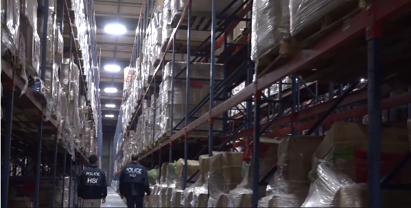 Two agents walk through a sea of seized counterfeit goods connected to the case. (Video still from U.S. Immigration and Customs Enforcement)