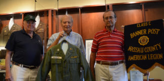 Anthony W. Buzzitta, flanked by two fellow veterans, holds up his old U.S. Army jacket. (Photo by Janelle Clausen)