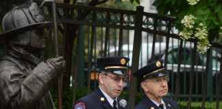 A statue of Jonathan L. Ielpi, a New York City firefighter from Great Neck, looms over Vigilant Fire Chief Joshua Charry as he addresses attendees, with his father Rabbi Marim Charry by his side. (Photo by Janelle Clausen)