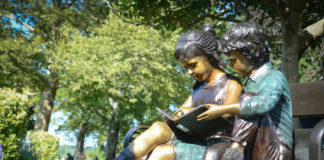 Two bronze children sit perched on a bench underneath a magnolia tree and adjacent to a memorial plaque for Ruth Tamarin. (Photo by Janelle Clausen)