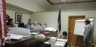 Architect Ronald Zakary reviews the revised building plans for Tower Ford with Thomaston Mayor Steve Weinberg, center left, and the board. (Photo by Samuel Glasser)