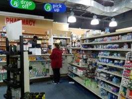 A pharmacist serves a customer on Monday, the last day the pharmacy was open. (Photo by Janelle Clausen)