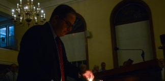 Rabbi Daniel Schweber of Temple Israel lights candles to honor the 11 people killed in the Tree of Life Congregation shooting. (Photo by Janelle Clausen)