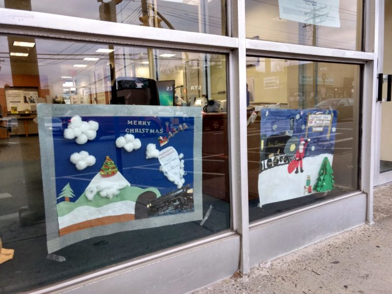 Handmade posters line Plandome Road in anticipation of annual tree lighting