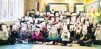 Students hold up the cards they created for troops serving overseas. (Photo courtesy of the Great Neck Public Schools)
