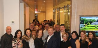 Great Neck Plaza Mayor Jean Celender, sales manager Samuel Marcus, and other guests prepare to cut the ribbon on the new Daniel Gale office. (Photo courtesy of Abby Sheeline of Daniel Gale Sotheby's International Realty)