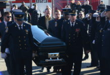 Tyler and Ryan Plakstis, Thomas McDonough Jr., and fire department officials carry Ray Plakstis up the steps of St. Aloysius Catholic Church. (Photo by Janelle Clausen)