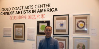 Shi Xiangdong standing in front of the his paintings stands in front of his work in the Gold Coast Art Center's new exhibit. (Photo by Demi Guo)