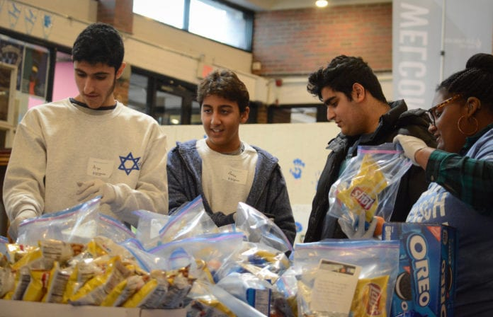 A group of teens work together to assemble bags of goods for the Interfaith Nutrition Network as part of the Martin Luther King Day of Service. (Photo by Janelle Clausen)