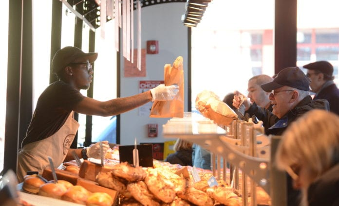 An employee of Marie Blachére passes along a baguette to one of the many customers on line ordering French pastries. (Photo by Janelle Clausen)