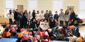 Eighth-graders from the North Middle School FACS program visited the John F. Kennedy School to deliver fleece hats and share a story with kindergarten students. Lauren Neckin, department chair for FACS, and her North Middle students are photographed with Kennedy School faculty Alyssa Gies, special education teacher; Christina Russo, kindergarten teaching assistant; Judy Friedman, kindergarten teacher; Ron Gimondo, principal; Michelle Reiter, kindergarten teacher; Gabby Kishinevsky, kindergarten teacher; and Michelle Bell, assistant principal. (Photo courtesy of the Great Neck Public Schools)