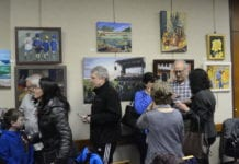 Artists, family and friends examine the work on display in Great Neck Plaza Village Hall. (Photo by Janelle Clausen)