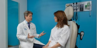 Dr. Mark L. Smith, executive director of the Friedman Center for Breast and Lymphatic Surgery, consults with a patient during an exam. (Photo courtesy of Northwell Health)