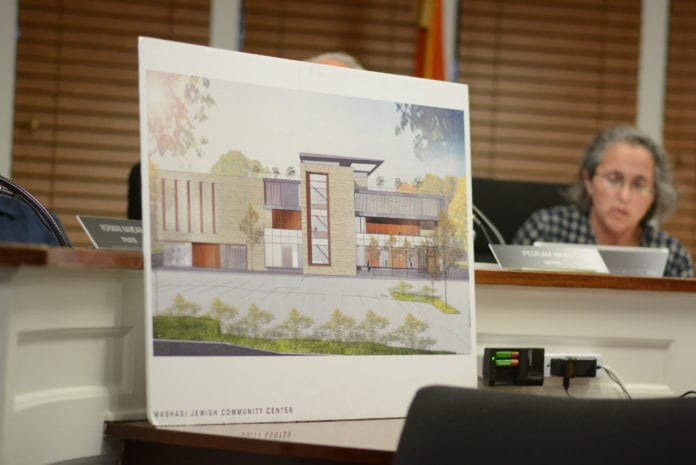 A rendering of the proposed recreational center for the United Mashadi Jewish Community of America sits in front of the Village of Great Neck Board of Trustees. (Photo by Janelle Clausen)